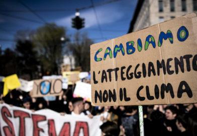 Manifestazione con cartello cambiamo atteggiamento non il clima