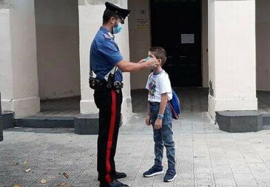 Un Carabiniere di fronte ad un bambino che va a scuola